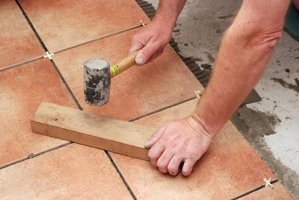Укладка плитки на пол выполняется с использованием резиновой киянки